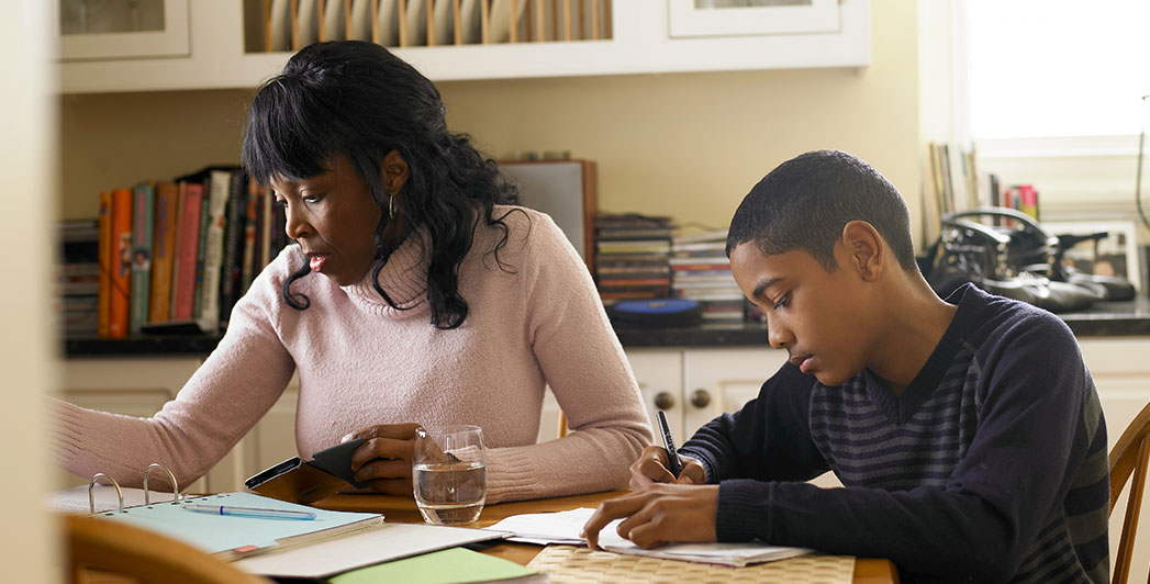 A mother in a pink sweater sits at a table holding a calculator and looks at a binder full of papers while helping her teenage son, sitting to the right of her, with his homework