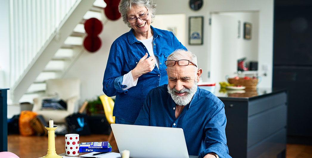 two senior citizens sit at a table working on a computer in their kitchen.